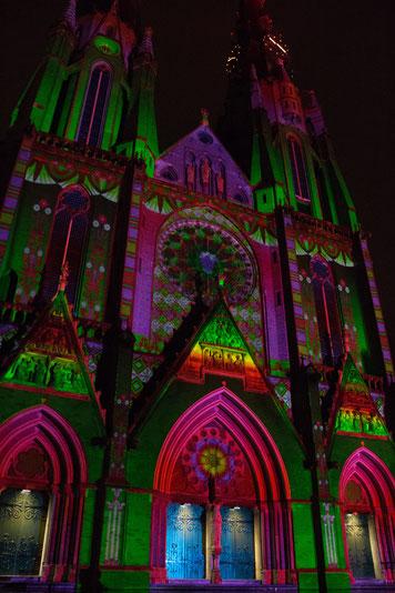 Een kerk met kleurbelichting. Hoofdkleuren rood en groen.