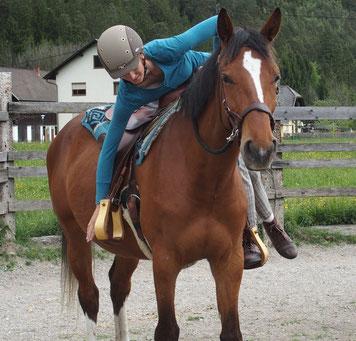 Natascha Leiler steigt vorsichtig auf ein Jungpferd auf