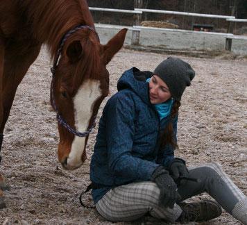 Ein Pferd senkt den Kopf zu der am Boden sitzenden Natascha Leiler