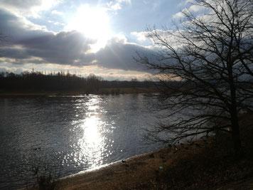 Sonne glitzert durch dicke Wolken und spiegelt sich im Fluss