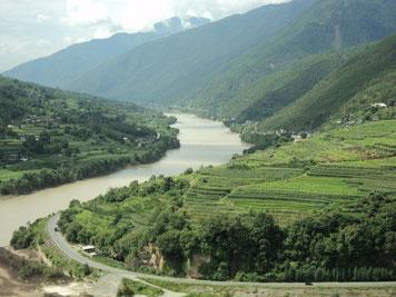 Saftig grünes Tal, das mit langem Fluss durchzogen ist