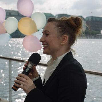 Hochzeitsrednerin mit See-Panorama und bunten Luftballons