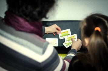 Foto: Frau Pevzner erklärt junger Schülerin die Rythmuskärtchen