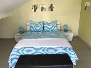 Ein grosser Kleiderschrank und ein Doppelbett bilden die Einrichtung des Schlafzimmers. Im Hintegrund hat man eine gute Aussicht durch das Fenster auf die gegenüberliegende Bucht