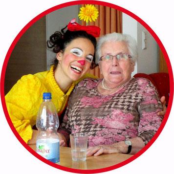 Gesundheits Clown Angelina Haug aus Esslingen umarmt eine Bewohnerin eines Pflegeheims, beide lachen und freuen sich des Lebens.