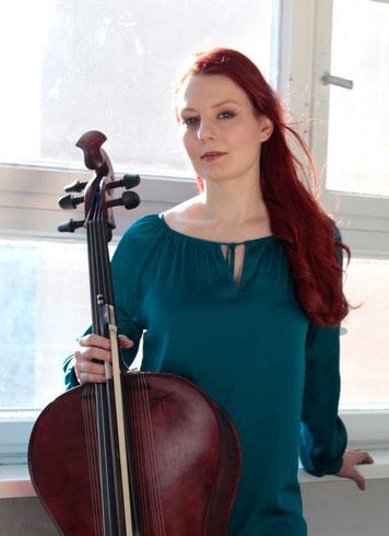 Cellistin mit roten langen Haaren und rotem Streichinstrument mit Resonanzsaiten - Stefanie John mit Campanula