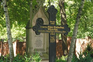 Passend zur Bach-Genealogie sieht man ein Kreuz verziert in schwarz mit einem Grabstein im Hintergrund. Es steht auf einem Friedhof unter Bäumen. Hinten sieht man die Sonne auf einigen Gräbern. Das Kreuz trägt eine Inschrift zur Bach-Genealogie.