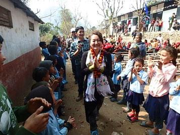 山道を超えていくと、学校の子ども達がお出迎え。村の皆さんの音楽隊とともに思わず踊りだす。