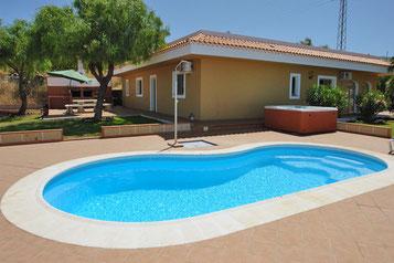 Im Vordergrund des Bildes ist der Pool von der Immobilie zu sehen und dahinter das Haus.