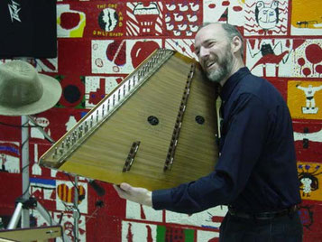 Sam holding up his hammered dulcimer at a school performance, so the audience can see it.
