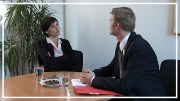 Szene aus dem Trainingsvideo zu Nonverbaler Kommunikation im Alltag: Er zeigt ihr Urlaubsfotos von allen Details der Reise - sie ist genervt.
