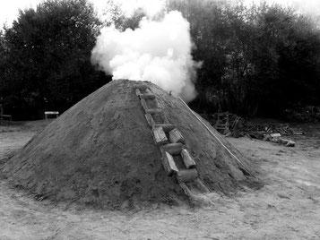 Carbonización lenta de madera en horno de tierra
