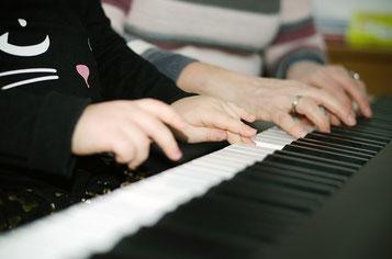 Foto: 4 Hände auf Klaviertasten