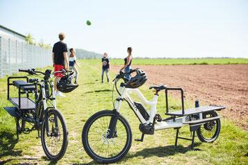 Eine Familie spielt hinter zwei XCYC Life Modellen mit einem Ball