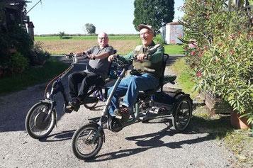 Zwei Kunden fahren auf ihren Dreirädern übers Feld