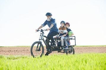 Mann mit Bart fährt mit dem XCYC Pickup Life und seinen zwei Kindern über ein Feld