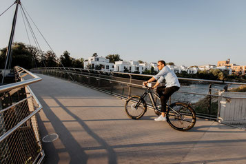 Mann fährt mit seinem neuen M1 Erzberg GT über eine Brücke