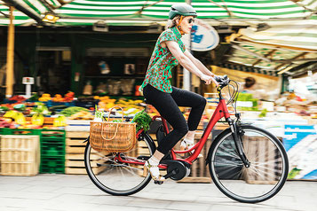 Frau mit e-Bike und Einkäufen Probefahrt