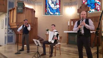 Drei Musiker spielen Instrumente