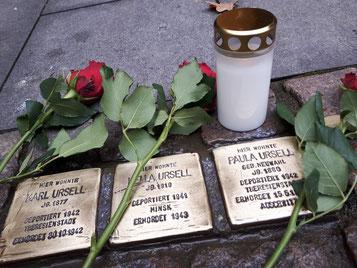 Drei Stolpersteine mit Blumen und Kerze.