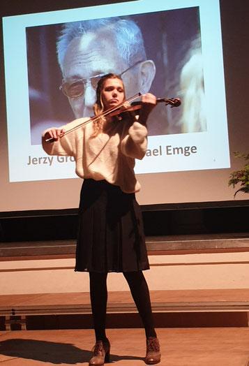 Die Geigerin Judith Stapf vor einem Bild von Jerzy Gross.