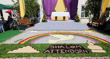 Aus Blumen gefertigter Schriftzug von Shalom Attendorn vor einem Altar