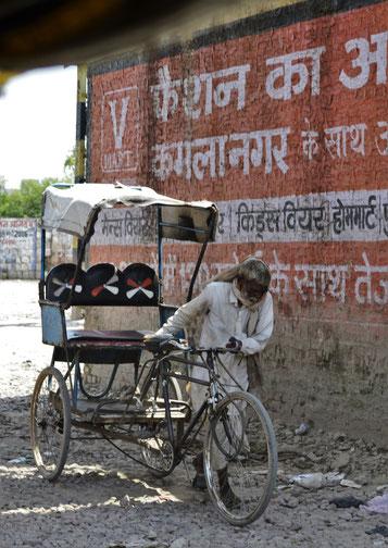 Das Leben auf indischen Straßen ist für alle kein leichtes    -                    ein Fahrradrikschafahrer auf der unbefestigten Straße nach Sikandra