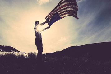 Mann mit amerikanischer Flagge in Sonnenuntergang