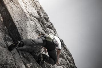 Mann in Felswand klettert