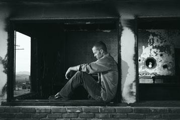 Mann sitzt gegen Säule und denkt nach