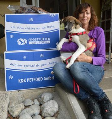Tierheimleiterin Ulrike Vogel freut sich mit Welpe Isis über zwei riesige Kartons voll mit leckeren Kauartikeln für unsere Hunde.