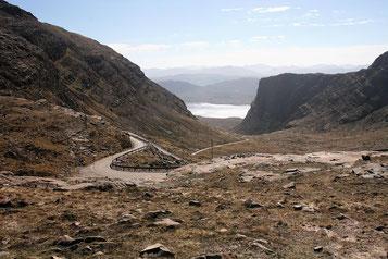 Eine schmale Straße windet sich den Applecross-Pass hinunter, im Hintergrund Berge und Wasser