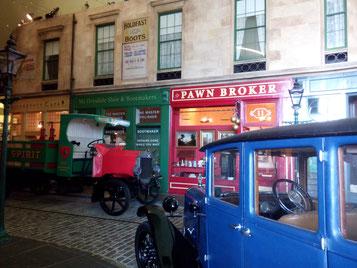 nachgebaute Straße im Riverside Museum mit alten Autos und historischen Geschäften