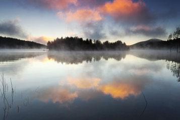 shore reflecting on lake at dusk