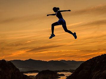 Eine Frau springt von Fels zu Fels im Sonnenuntergang (Foto).