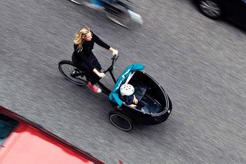 Frau fährt mit ihrem Kind in Triobike durch die Stadt