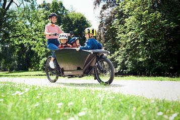 Eine Frau fährt mit 3 Kindern im Lasten e-Bike