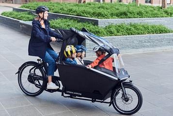 Frau fährt drei Kinder mit dem Urban Arrow Family von A nach B