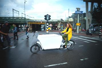 Ansehen von Lastenvelos steigt - Frau fährt mit dem Lastenrad von Urban Arrow