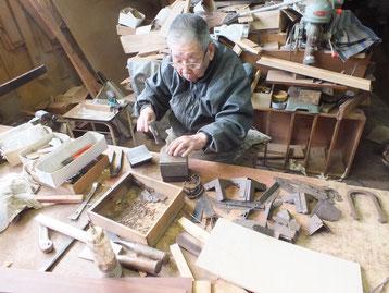 東京都より修理依頼の時代箪笥の外した多くの金物を叩き伸ばし形を整えています。