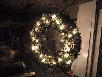 巨大なクリスマスリースの白熱球のイルミネーションを点灯