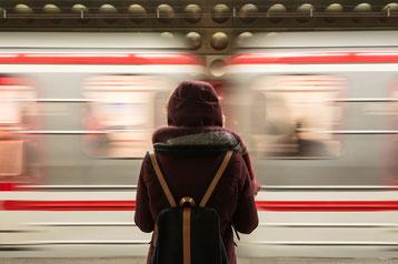 Dame in Station beobachtet fahrenden Zug