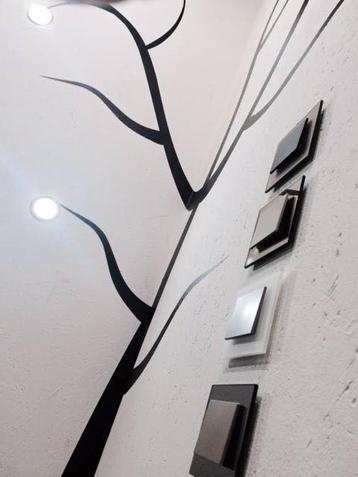 photo présentant 4 interrupteurs va et vient au design moderne en verre de couleur noir, blanc mat, effet miroir et moka positionné à la verticale sur un mur crépi blanc.