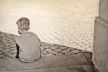 trauriges Kind sitzt auf Treppe