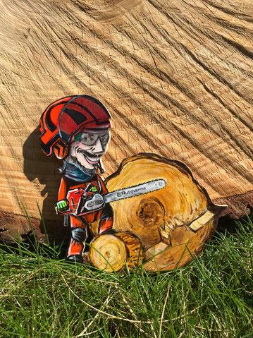 Karikaturporträt als Magnet für Pinnwand, Kühlschrank, Memoboard. Baumpfleger in Schutzausrüstung und mit seiner Kettensäge von Husqarna vor einer riesigen Baumscheibe.