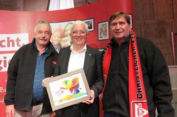 Michael Kühn (links) und Manfred Wille (rechts) übergeben ein farbenfrohes Bild mit einem Elefanten, der im Rüssel das Logok zum 175-jährigen Jubiläum trägt, an Karl-Heinz Stengel