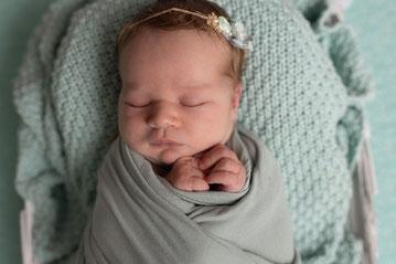 Newborn Shooting, Berg-Fotomomente, Baby schlafendes Mädchen im Körbchen, braunes Spitzenbody, auf brauner Kammzugdecke, mit gelben Blumen und gelbes Spitzentuch