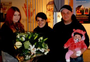 Die Heinz von Heiden-Bauherrenfachberaterin Carolin Lambert überrascht Xenia Görg, Matthias Schwarz und die kleine Lili mit der Neuigkeit, dass sie die 46.000-sten Bauherren sind.