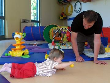 Vater spielt mit Kind im Familienzimmer
