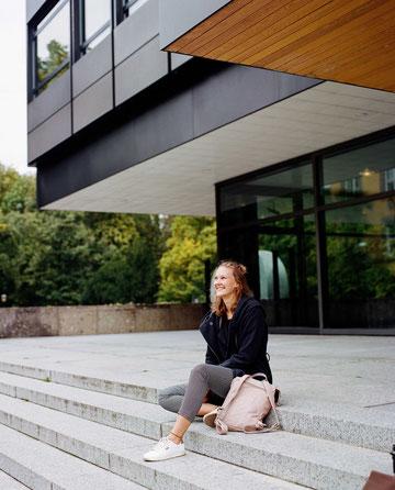 Die Gründerin Sandra Dombrowski sitzt auf einer Treppe und schaut glücklich in den Himmel.